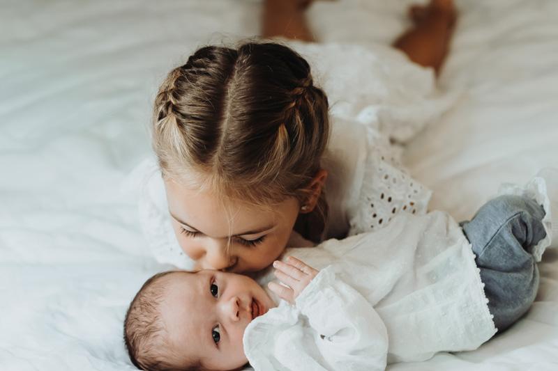 meisje kust pasgeboren broertje